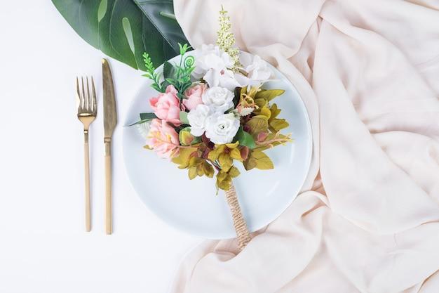 Bouquet di rose, posate e piatto sulla superficie bianca. Foto Gratuite