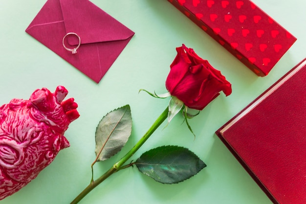 Rose branch with envelope and wedding ring Free Photo