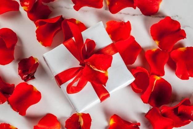Rose flower petals and white wrapped gift box with red ribbon on white marble background Premium Photo