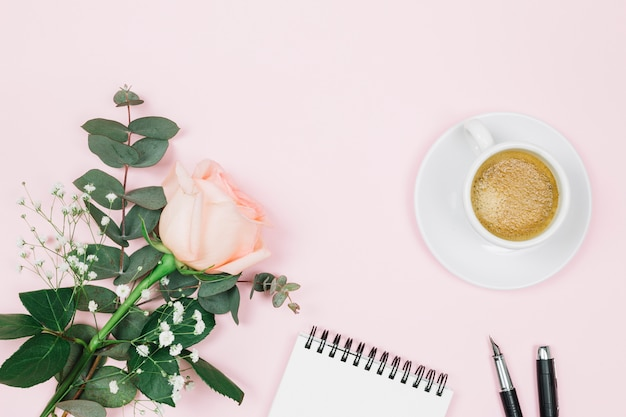 Rose flower with coffee; spiral notepad and fountain pen on pink background Free Photo