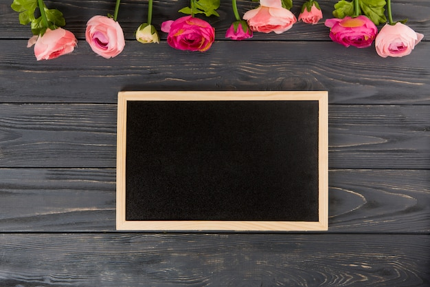 Rose flowers with big chalkboard on wooden table Free Photo