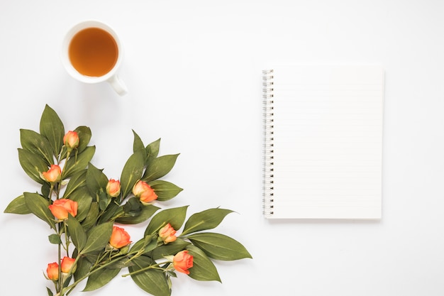 Rose flowers with notebook and tea cup Free Photo