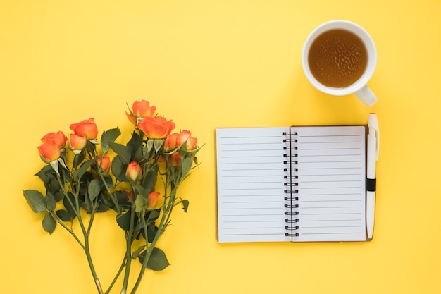 Rose flowers with notebook and tea on table Free Photo