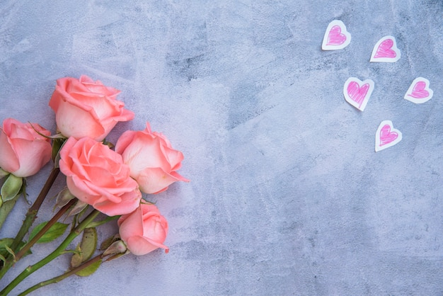 Rose flowers with paper hearts on table Free Photo