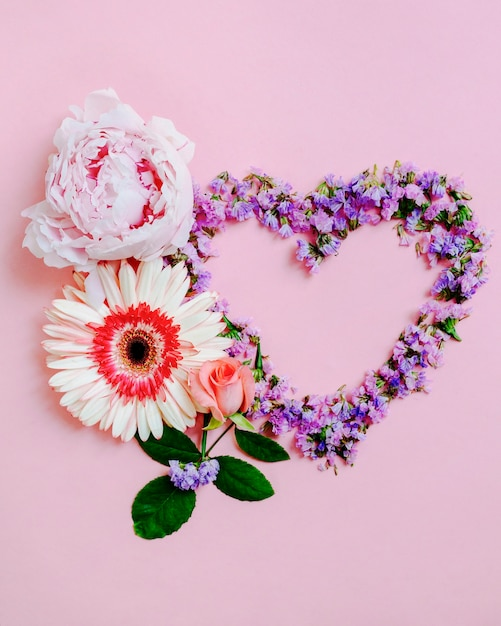 Rose, gerbera and peony flower with heart shape on pink background Free Photo