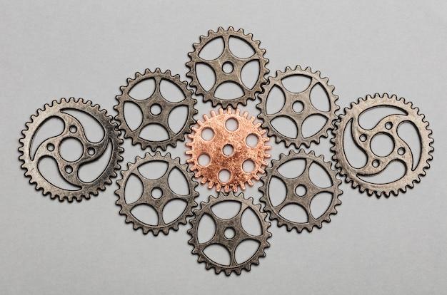 Rose-gold cogwheel and bunch of silver cogwheels Premium Photo