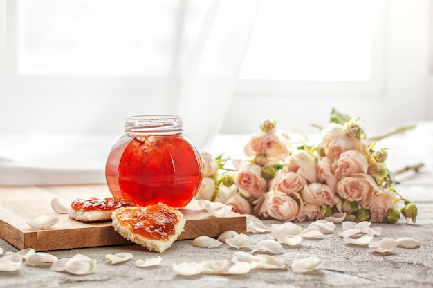 Rose petal jam and heart shaped sandwich with marmalade rose flower on table. Premium Photo