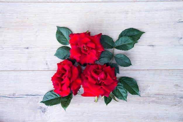 木製の灰色の背景には、赤い花の配置をバラ Premium写真