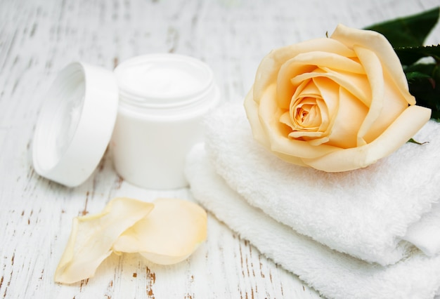 Rose with moisturiser cream and towels Premium Photo