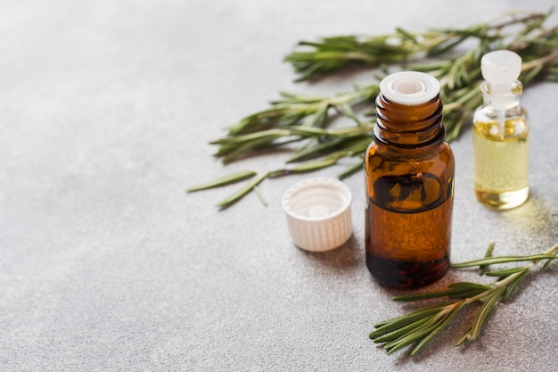 Rosemary essential oil in a glass bottle with fresh branch rosemary herb Premium Photo