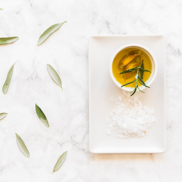 Rosemary and garlic cloves oil in bowl with salt on white tray Free Photo