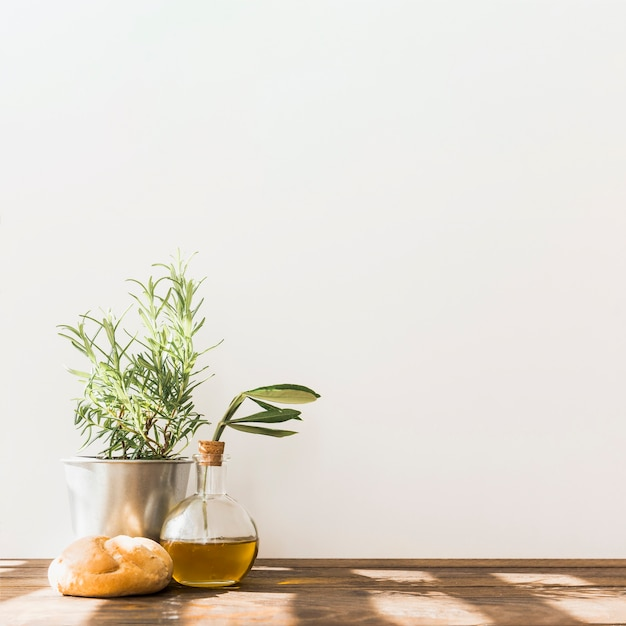 Rosemary pot with fresh olive oil bottle and bun on wooden table Free Photo