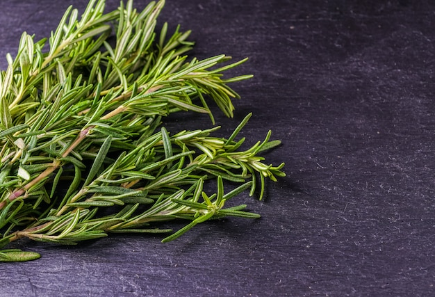 Rosemary and thyme on the black background, top view. Premium Photo