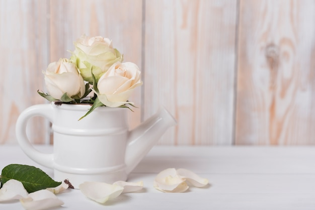 Roses in the ceramic small watering can on wooden desk Free Photo