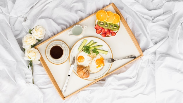 Roses and healthy breakfast tray on crumbled bed Free Photo
