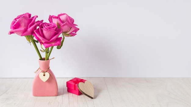 テーブルの上のギフトボックスと花瓶のバラ Premium写真
