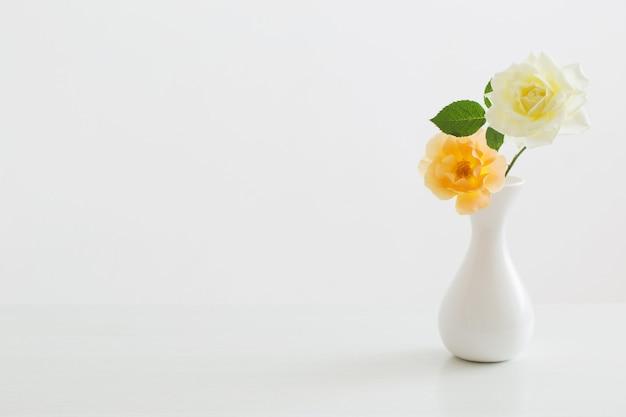 白い背景の上の白い花瓶のバラ Premium写真