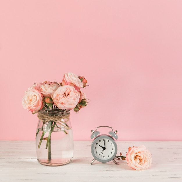 Roses vase near the alarm clock on wooden desk against pink background Free Photo
