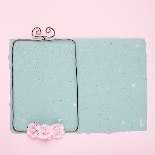 Roses on wired frame over the blue paper on pink backdrop Free Photo