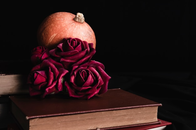 Roses with pumpkin on books Free Photo