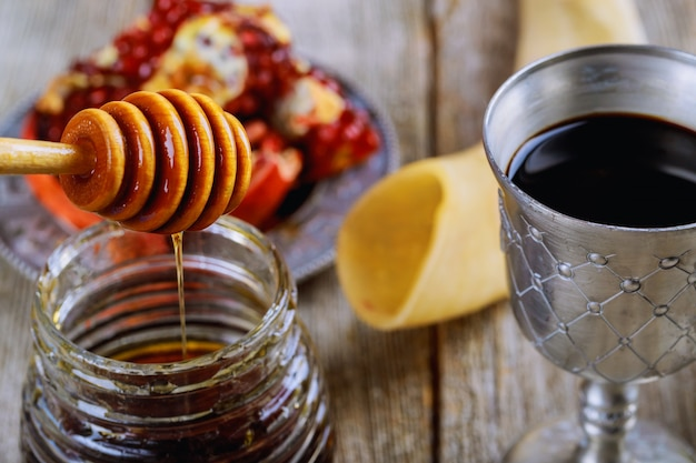 Rosh hashanah jewish holiday concept shofar, torah book, honey, apple and pomegranate. Premium Photo
