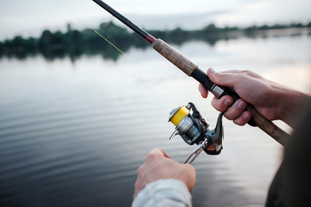 Rotative spinner that guy holds in hands. he rotates reel with left hand. he is at lake. it is evening outside. Premium Photo