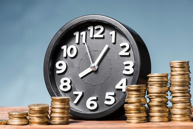 Round alarm clock with stack of increasing coins against blue background Free Photo