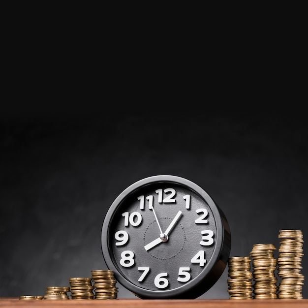 Round black alarm clock between the stack of golden coins against black background Free Photo