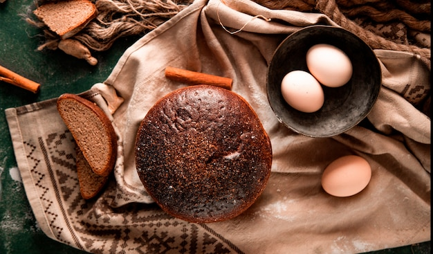 Round black bread with slices, cinnamon and egg bowl on a green table. Free Photo