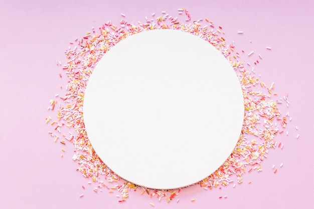 Round blank white frame surrounded with sprinkles on pink background ...