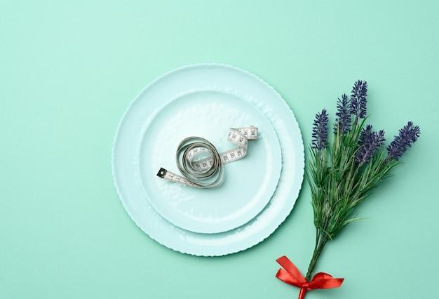 Круглая керамическая тарелка и сантиметр как концепция похудения Premium Фотографии