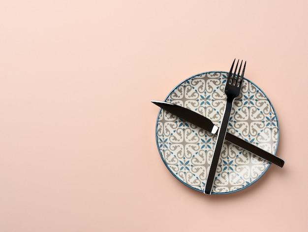 Круглая керамическая тарелка, скрещенные нож и вилка Premium Фотографии