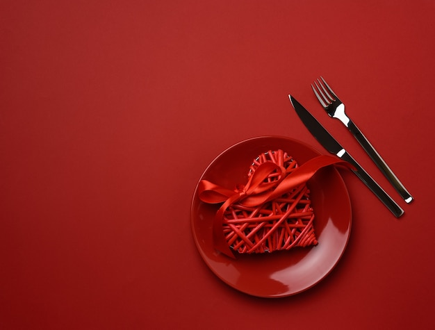 Круглая керамическая тарелка и вилка с ножом на красном фоне Premium Фотографии