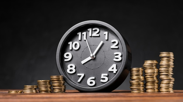 검은 배경 나무 책상에 증가 동전 사이의 라운드 시계 무료 사진
