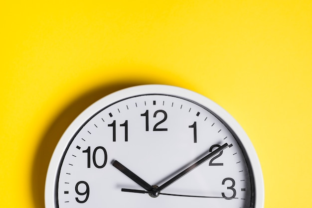 Round clock face against yellow backdrop Free Photo