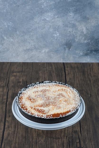 木製のテーブルに置かれた丸いおいしいケーキ。 無料写真