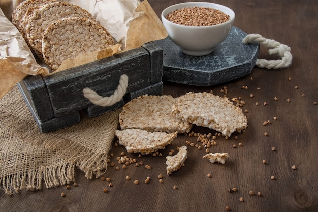 Round dietary loaves of airy buckwheat  and a cup of raw buckwheat Premium Photo
