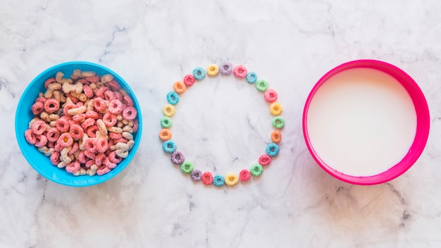 Round frame from cereals with bowls on table Free Photo