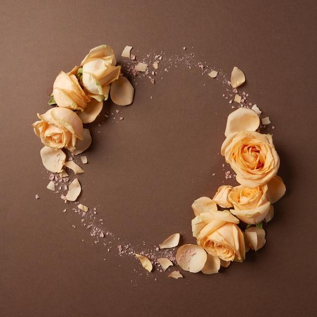 茶色の背景にベージュのバラの丸いフレーム、フラットレイ Premium写真