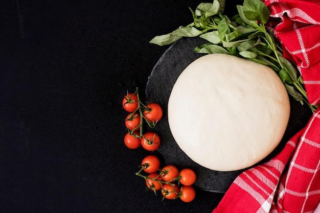 Round freshly bread dough; cherry tomatoes; basil and napkin on black background Free Photo