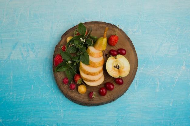 Круглое фруктовое ассорти с грушами, яблоком и ягодами посередине Бесплатные Фотографии