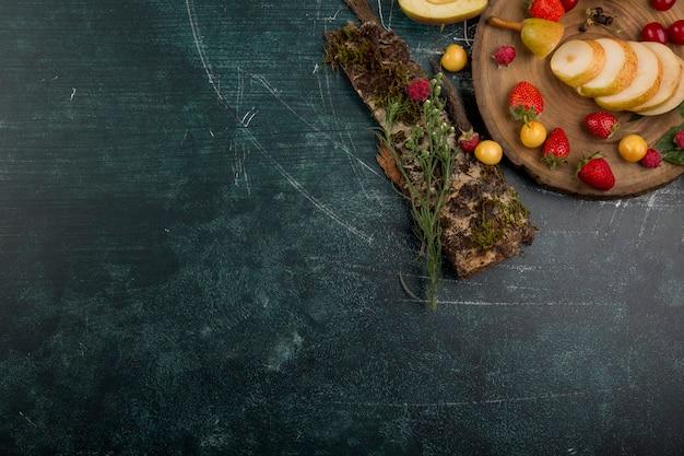 Круглое блюдо с фруктами, грушами, яблоками и ягодами на синем фоне в углу Бесплатные Фотографии