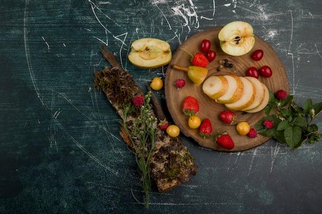 梨、リンゴ、青の背景、上面に分離された果実と丸いフルーツの盛り合わせ 無料写真