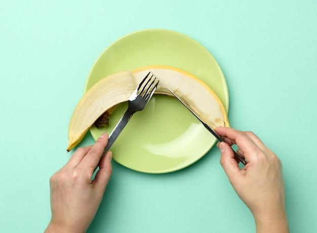 丸い緑色のセラミックプレートとバナナ全体の両手でナイフとフォークを持ちます Premium写真