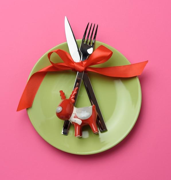 Круглая зеленая тарелка, металлическая вилка и нож, перевязанные красной шелковой лентой Premium Фотографии