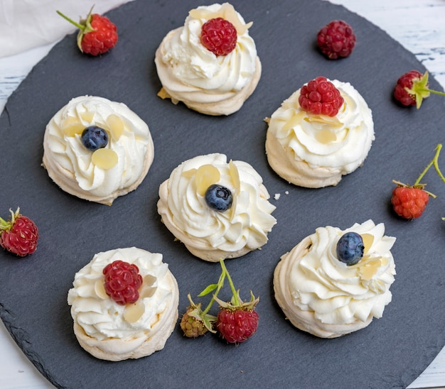 Round meringues with whipped cream on a black graphite board Premium Photo