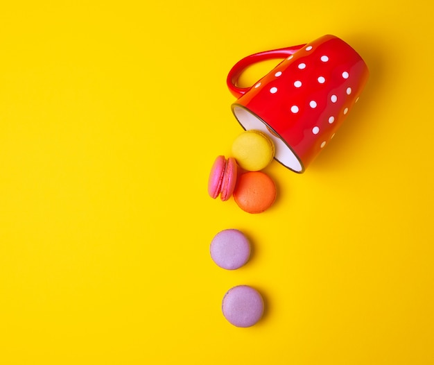 Round multicolored macarons falling from a red ceramic cup Premium Photo