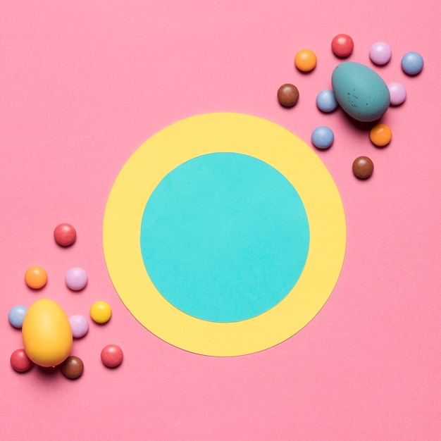 Round paper frame decorated with gem candies and easter eggs on pink background Free Photo