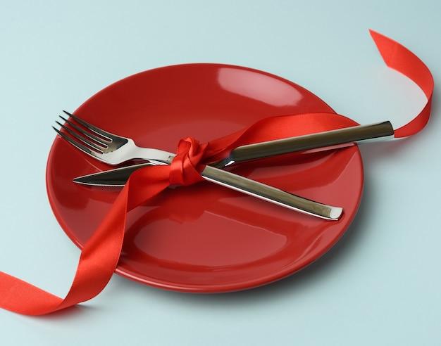 Круглая тарелка, металлическая вилка и нож, перевязанные красной шелковой лентой Premium Фотографии