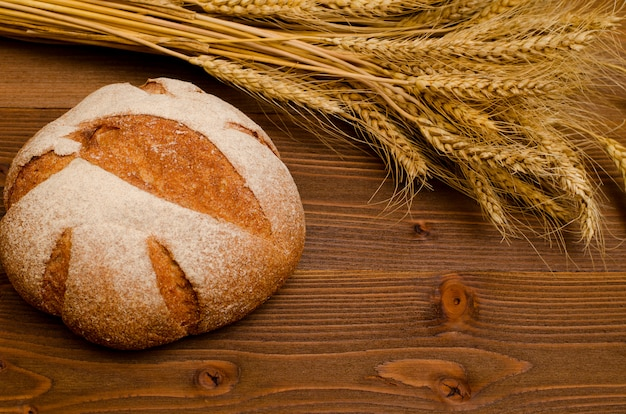 Round rye bread and ears of wheat on a wooden table, top view Premium Photo